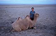 Mongolia, Gobi desert. July 1996: One of Munkhtsetseg's family poses with a camel in the Gobi desert.