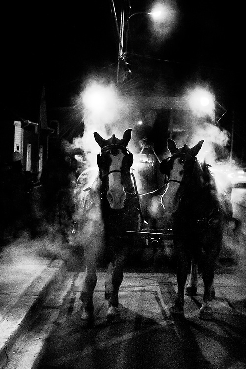 Street Photography taken in Bloomfield, Prince Edward County in December 2019 at a night time Santa Claus Parade. The horses were pulling a wagon ride.