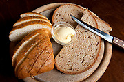 Fresh baked whole wheat bread and butter on a wooden platter