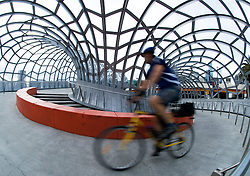 Cyclist crossing dramatic steel Webb Footbridge in Doclands Melbourne Australia
