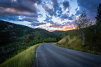 The alpine roads wind through the Wasatch Mountains at sunset as the first signs of Fall colors begin to show in the trees.
