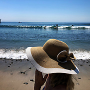 Enjoying life at Malibu's famous Surfrider Beach in the shade of a summer hat.