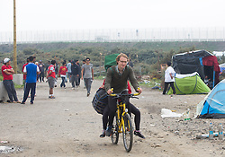 """© Licensed to London News Pictures. 30/08/2015. Calais, France. One of the British cyclists from """"Critical mass to Calais"""" arrives to the refugee camp, also known as the Jungle, after riding from London to donate bicycles and supplies to support the life at the site. Photo credit : Isabel Infantes/LNP"""