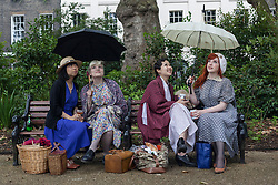 © licensed to London News Pictures. London, UK 08/07/2012. People waiting for the rain to stop at the Chap Olympiad in Bedford Square Gardens in central London today.the Chap Olympiad describes itself as a celebration of eccentricity and athletic ineptitude with the emphasis on panache and style over sporting prowess. Photo credit: Tolga Akmen/LNP