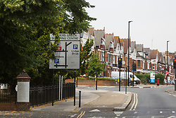 Bus stop signage, the bus stop itself as well as cycling signage and overgrown tree foliage obscure a directional sign on Green Lanes in Southgate, London. Trees and other objects are obscuring motorists' views of roadsigns that often impart crucial speed or safety information. London, July 17 2019.