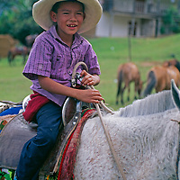 A youngster rides a horse Yamblon, Peru.