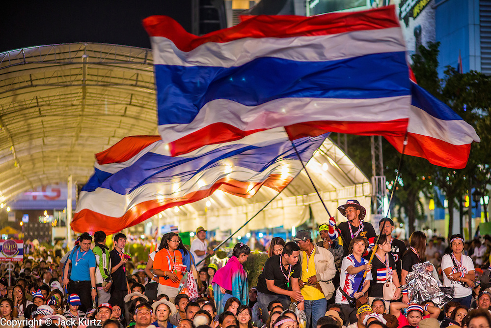 24 JANUARY 2014 - BANGKOK, THAILAND: Thai anti-government protestors wave Thai flags at the Pathum Wan Shutdown Bangkok protest site while she waits for Suthep Thaugsuban. Shutdown Bangkok has been going for 12 days with no resolution in sight. Suthep, the leader of the anti-government protests and the People's Democratic Reform Committee (PDRC), the umbrella organization of the protests,  is still demanding the caretaker government of Prime Minister Yingluck Shinawatra resign, the PM says she won't resign and intends to go ahead with the election.    PHOTO BY JACK KURTZ