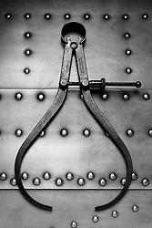 caliper tool on riveted metal fuselage background