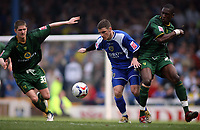 Cardiff Citys Jason Koumas tries to break past Carl Robinson (left) and Dickson Etuhu (right)