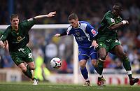 Cardiff Citys Jason Koumas tries to break past Carl Robinson (left) and Dickson Etuhu (right)