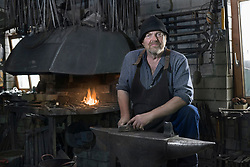 Portrait of senior blacksmith in traditional workshop, Bavaria, Germany