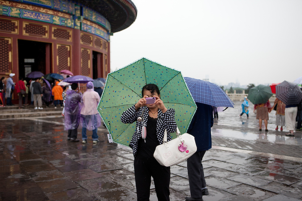 "Woman with umbrella  photographing at ""The Temple of Heaven"" which is a complex of Taoist buildings situated in the southeastern part of central Beijing. Beijing is the capital of the People's Republic of China and one of the most populous cities in the world with a population of 19,612,368 as of 2010."