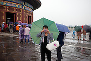 """Woman with umbrella  photographing at """"The Temple of Heaven"""" which is a complex of Taoist buildings situated in the southeastern part of central Beijing. Beijing is the capital of the People's Republic of China and one of the most populous cities in the world with a population of 19,612,368 as of 2010."""