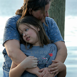 Becky Ammar hugs her youngest daughter, Marie, 9, on the dock behind their home.  The Great American Backyard Campout would be the last weekend they occupied their farm before it was sold...Photo by Susana Raab