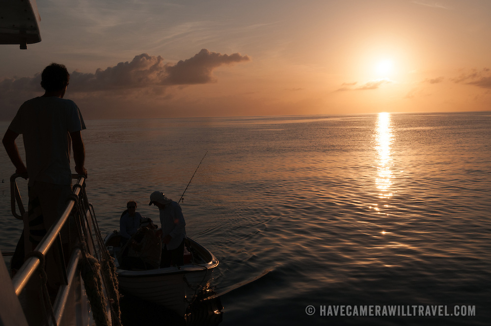A small fishing boat returns back to the mother ship at the end of a day of fishing on the Great Barrier Reef, Queensland, Australia. The boat itself is silhouetted against a calm sea and setting sun, and a deckhand on the big boat at far left gets ready to grab the bow line.