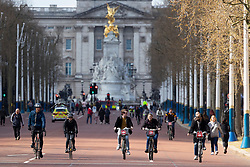 © Licensed to London News Pictures. 11/04/2021. London, UK. Members of the public cycle on the The Mall in central London during sunny conditions. Temperatures are expected to rise with highs of 15 degrees forecasted for parts of London and South East England later this week . Photo credit: George Cracknell Wright/LNP