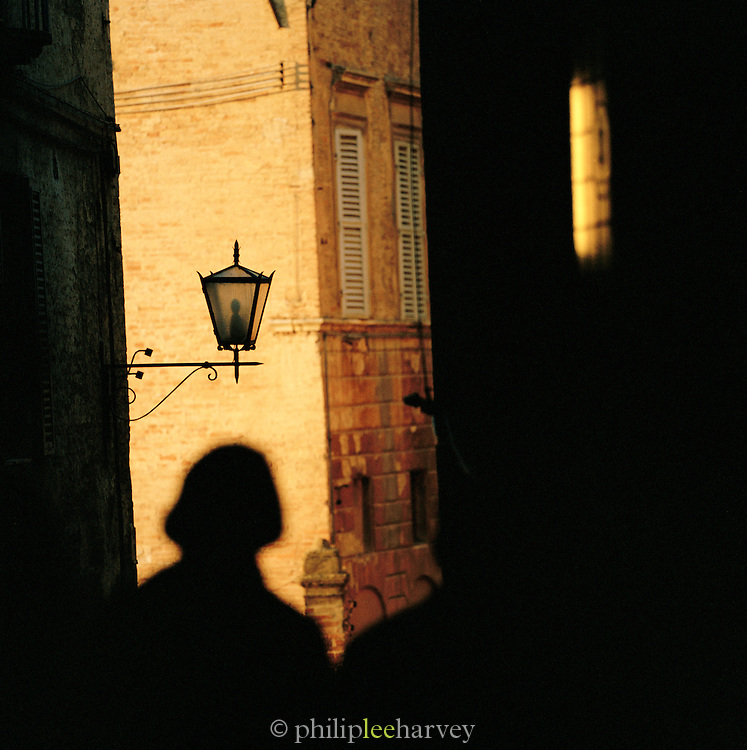 Tourists silouhetted in the back streets of the Old Town, Siena, Tuscany, Italy