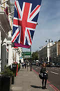 British Union Jack flags hanging outside small hotels on Cromwell Road, Kensington in London, England, United Kingdom.