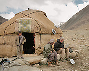 """Paul Salopek working on his computer in front of a yurt at a Wakhi high pasture names """"Warm"""", below Garumdee Pass. Guiding and photographing Paul Salopek while trekking with 2 donkeys across the """"Roof of the World"""", through the Afghan Pamir and Hindukush mountains, into Pakistan and the Karakoram mountains of the Greater Western Himalaya."""