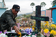 A man decorates the gravesite of a departed loved one, Sumpango Cemetary, Guatemala.