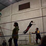 Carman Rosa (centre) receives advice from El Cobarde  during a late evening training session with other members of the 'Titans of the Ring' at a makeshift gymnasium in El Alto, Bolivia . The wrestling group performs every Sunday at El Alto's Multifunctional Centre. Bolivia. The group includes the fighting Cholitas, a group of Indigenous Female Lucha Libra wrestlers who fight the men as well as each other for just a few dollars appearance money. El Alto, Bolivia, 28th January 2010. Photo Tim Clayton
