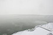 Uitzicht naar het Ijsselmeer vanaf de Afsluitdijk met sneeuw, verbinding tussen Den Oever op Wieringen,  Noord Nederland en Zurich, Friesland..View to the Iisselmeer from the Afsluitdijk (Enclosure Dam) with snow, a major causeway in the Netherlands, constructed between 1927 and 1933 and running from Den Oever on Wieringen in North Holland province, to the village of Zurich in Friesland province, over a length of 32 km (20 miles) and a width of 90 m, at an initial height of 7.25 m above sea-level.