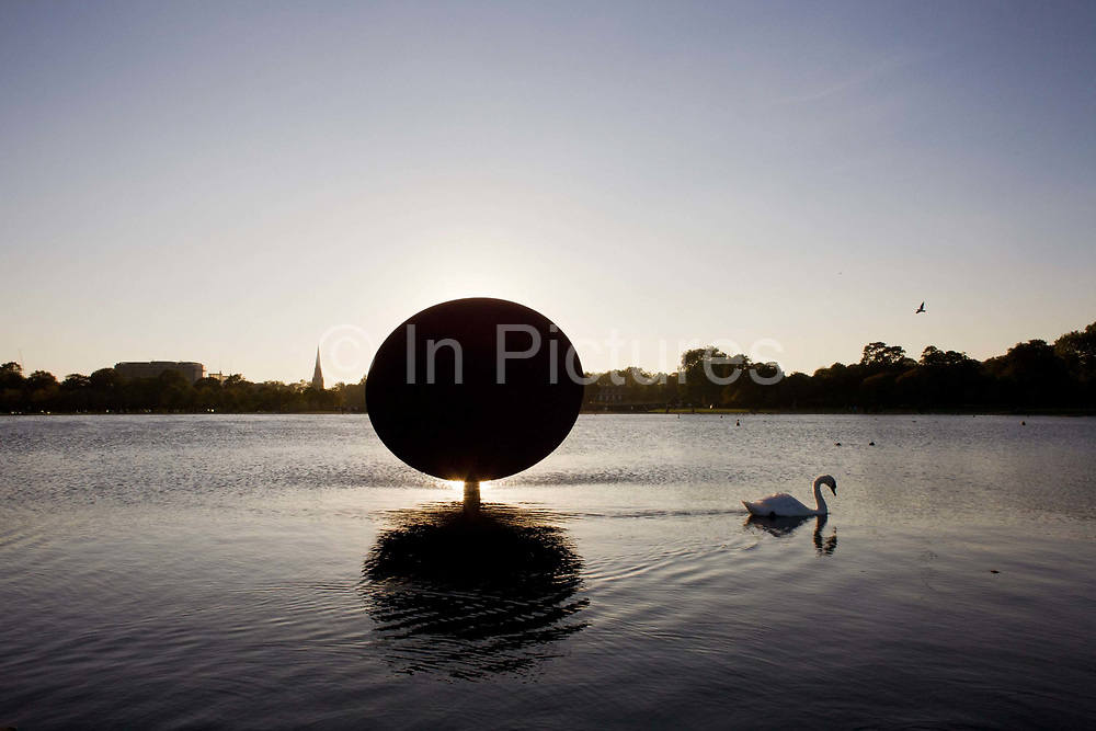 A swan sedately paddles past artist Anish Kapoor's artwork called Sky Mirror, part of his Turning the World Upside Down show in Kensington Gardens. The Royal Parks and the Serpentine Gallery presented a major exhibition of large-scale outdoor sculptures by acclaimed London-based artist Anish Kapoor in Kensington Gardens. The free exhibition showcased a series of major recent works never before shown together in London. Constructed from highly reflective stainless steel, the giant curved mirror surfaces will create illusory distortions of the surroundings and will be visible across large distances, creating new vistas in this famous and much-loved setting. The sculptures were sited to contrast and reflect the changing colours, foliage and weather in Kensington Gardens.