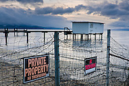 Private Property No Trespassing sign on fence along the beach at South Lake Tahoe, California