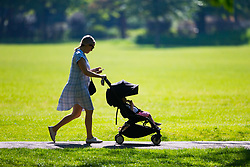 A woman pushes her toddler in a buggy in Queen's Park, North West London, May 08 2018.