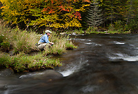 Jay Ericson sits quietly on the stream bank while fly fishing for trout on the upper Connecticut River in northern New Hampshire.