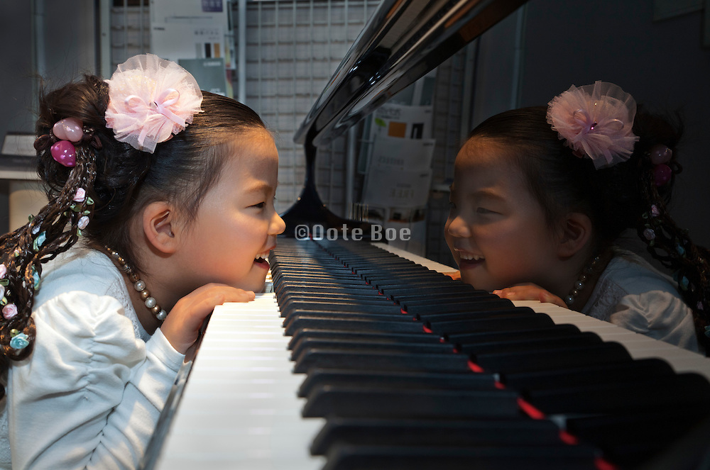 little girl smiling while looking at her self reflection within the piano