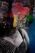 Adult shop costume image and red hat with reflections of central London in the background. The bosoms of a large woman are seen in a spiky, low-cut top and the red hat floats above the reflections of buildings from St Giles in Westminster. The shop is typical of Soho, selling adult-themed books and assorted .. accessories.