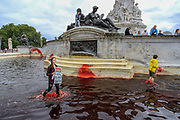 """An Animal and climate activist from the Animal Rebellion activists group holds up a placard that reads """"Animal Agriculture, a ROYAL Blood Bath"""" as they walk in the red-colour dyed fountain outside Buckingham Palace on Thursday, Aug 26, 2021 - signifying as their statement said """"its' demonstrable role in hunting and animal agriculture"""". (VX Photo/ Vudi Xhymshiti)"""