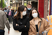 People out and about in the shopping district of Oxford Street, some wearing face masks and others not on 26th May 2021 in London, United Kingdom. As the coronavirus lockdown continues its process of easing restrictions, more and more people are coming to the West End as more retail businesses open.
