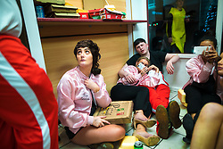 © Licensed to London News Pictures . 27/12/2017. Wigan, UK. People sit on the floor inside a takeaway . Revellers in Wigan enjoy Boxing Day drinks and clubbing in Wigan Wallgate . In recent years a tradition has been established in which people go out wearing fancy-dress costumes on Boxing Day night . Photo credit: Joel Goodman/LNP