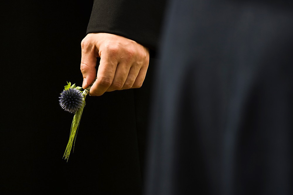 A bridegroom holds a small bouquet of dried flowers in his hand as he prepares to be married at an outdoor wedding in Rainier, Washington.