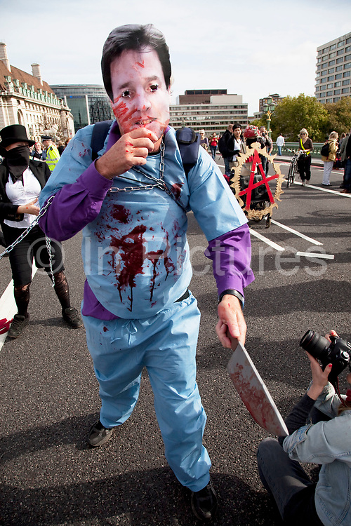 """Protesters dressed as Nich Clegg and David Cameron slash and cut with bloody knives at those standing by, in an act as if they were butchers or murderers cutting the NHS. UK Uncut shut down Westminster Bridge in a protest over NHS bill. Thousands of protesters occupied one of London's most iconic landmarks on 9 October, in a last-ditch attempt to defeat legislation that is condemned by doctors as 'undermining all that is precious about the NHS'. The anti-austerity direct action group demonstration blocked Westminster Bridge at 1pm on Sunday 9 October, days before the final vote in the House of Lords. The bill, which will see private patients treated at the expense of NHS patients, healthcare workers made redundant and reduce the priority of treating chronic and complex conditions, will be voted on by the Lords on the 12th October. The British Medical Association, the professional association of doctors in the UK, says the Bill """"presents unacceptable risks to the NHS"""" and is calling for the Bill to be withdrawn."""