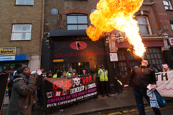 © Licensed to London News Pictures. 07/11/2015. London, UK. A protester breathes fire during a protest by Class War and supporters outside the Jack the Rippper Museum in Cable Street, Shadwell, east London. Protesters want to shut the museum down, accusing museum owner, Mark Palmer-Edgecumbe of glorifying rape and sexual violence against women. The original planning application for the museum submitted to Tower Hamlets council stated that it would celebrate the lives and history of east end women. This week a retrospective planning application for the museum sign and frontage was refused by the council.  Photo credit : Vickie Flores/LNP
