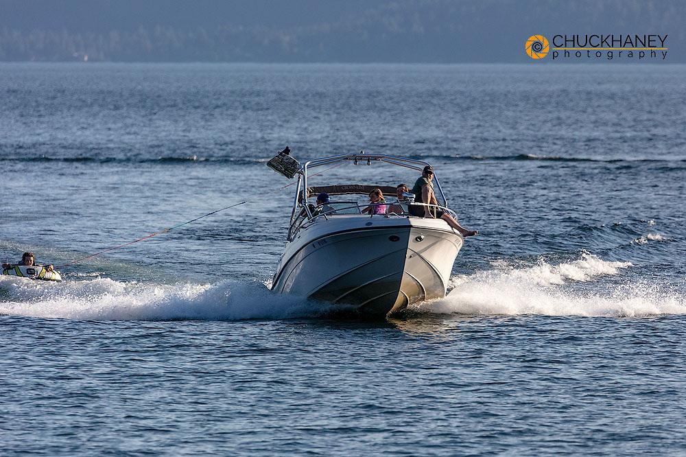 Power boat pulling tuber on Flathead Lake from Wayfarers State Park in Bigfork, Montana, USA