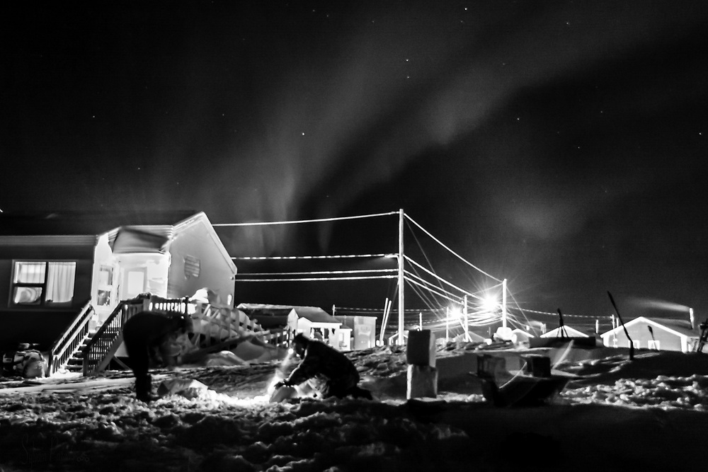 An aurora borealis decorated the background of the scene where two men inuk are cutting blocks of snow to clear out a qamutik.