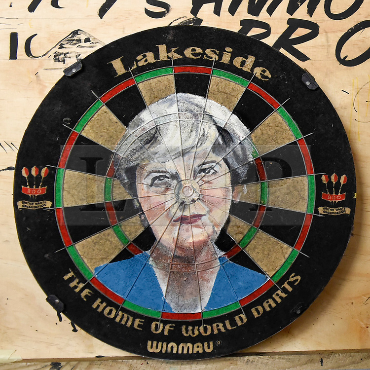 """© Licensed to London News Pictures. 17/08/2018. LONDON, UK. An images of Theresa May painted onto a dartboard by Zara Gaze at """"Letterheads 2018: London Calling"""", an international gathering of professional sign writers and lettering artists from over 30 countries.  The event is taking place at the Bargehouse, Oxo Tower Wharf in central London untikl 19 August.  Photo credit: Stephen Chung/LNP"""