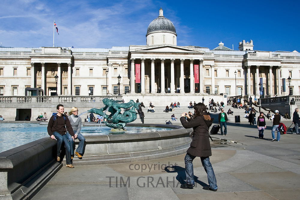 Tourists pose for photographs in Trafalgar Square by National Gallery, London, United Kingdom