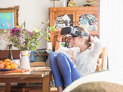 Girl wearing virtual reality glasses in living room