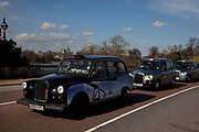 Three London cabs / taxis in a line.