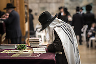 A man in a tallit shawl and hat, prays inside men's section of Wilson's Arch at the Western Wall. On the velvet table cloth embroidered with a representation of the second temple. bunches of fresh mint. Scent plays a role at the departure of Shabbat. When the spiritual high of Shabbat leaves us, we need refreshment. Hence smelling spices or fresh herbs are part of the havdalah ritual. Havdalah is a Jewish religious ceremony that marks the symbolic end of Shabbat. The ritual involves lighting a special havdalah candle with several wicks, blessing a cup of wine and smelling sweet spices.