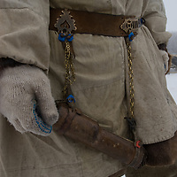 North of the Arctic Circle in Russia, a nomadic Komi reindeer herder displays his knife scabbard that hangs from a traditional decorated belt.