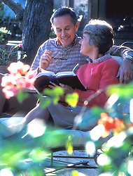 Stock photo of an older couple sitting and reading on outdoor patio furniture
