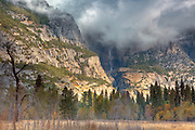 yosemite valley, yosemite falls. storm cloud hanging over yosemite falls illuminating the valley below