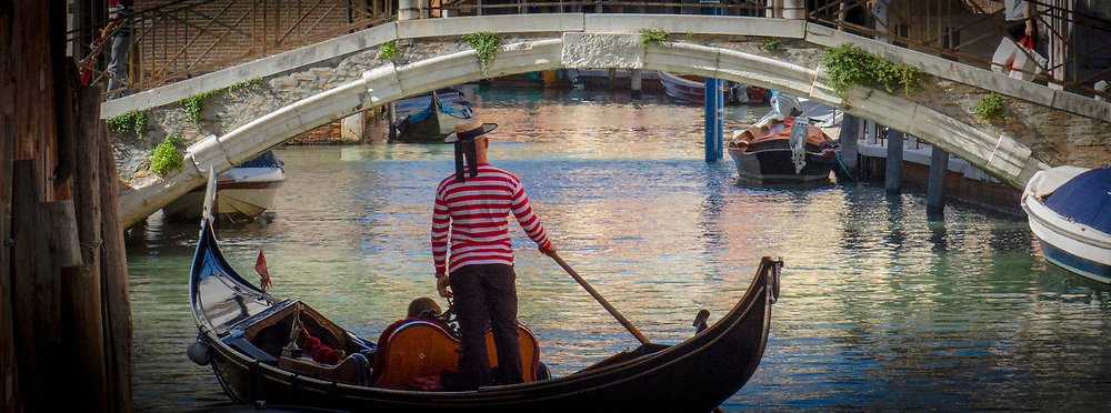 Gondolier with the traditional striped shirt and hat standing in a gondola approaching a bridge  in a Venice canal