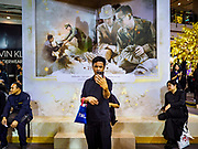 """25 OCTOBER 2017 - BANGKOK, THAILAND: A man in a Bangkok shopping mall takes a """"selfie"""" in front of art work of the King during the funeral for Bhumibol Adulyadej, the Late King of Thailand. He died in October 2016 and was cremated during an ornate five day funeral on 26 October 2017. He reigned for 70 years and was Thailand's longest serving monarch.         PHOTO BY JACK KURTZ"""